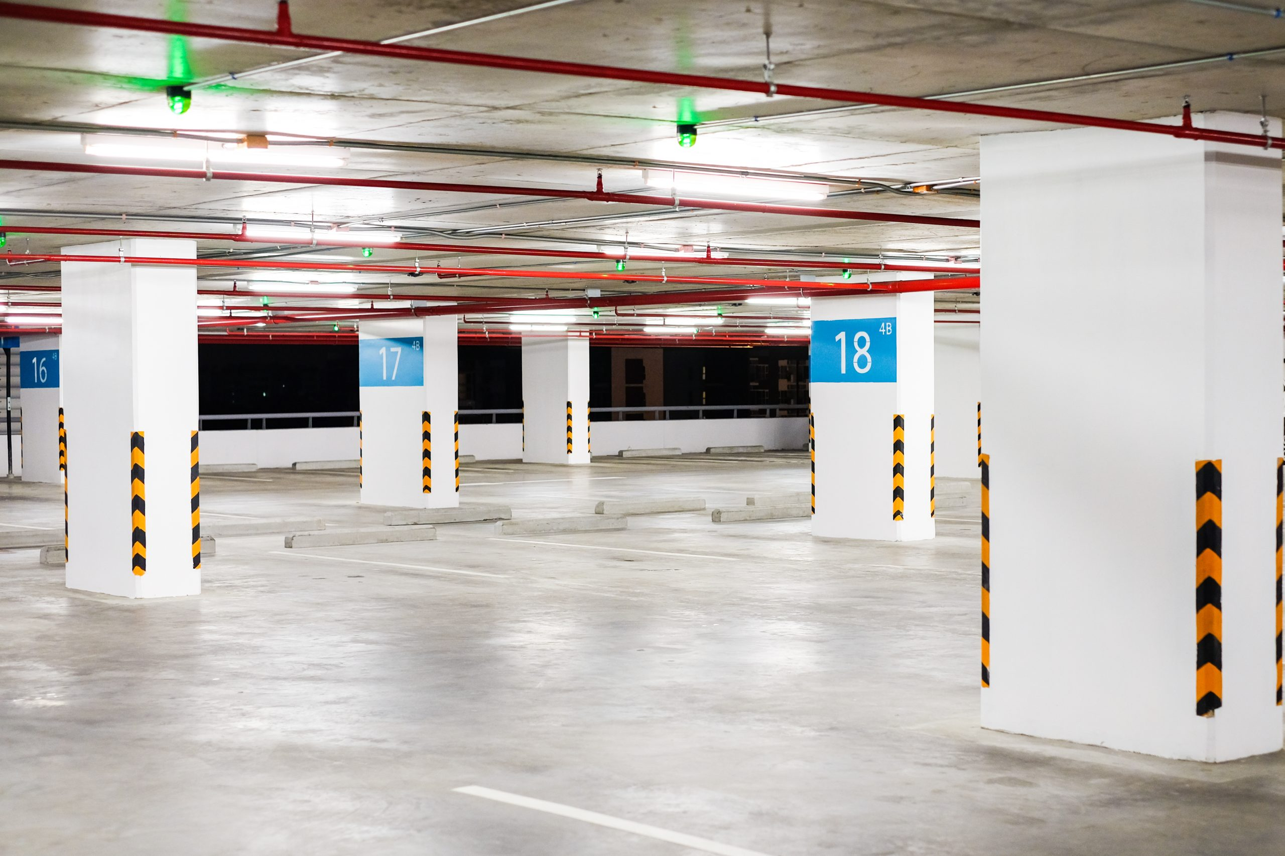 """Interior car park zone with white line for car and green sensor wireless control on ceiling for status """"blank or free"""" - business concept."""